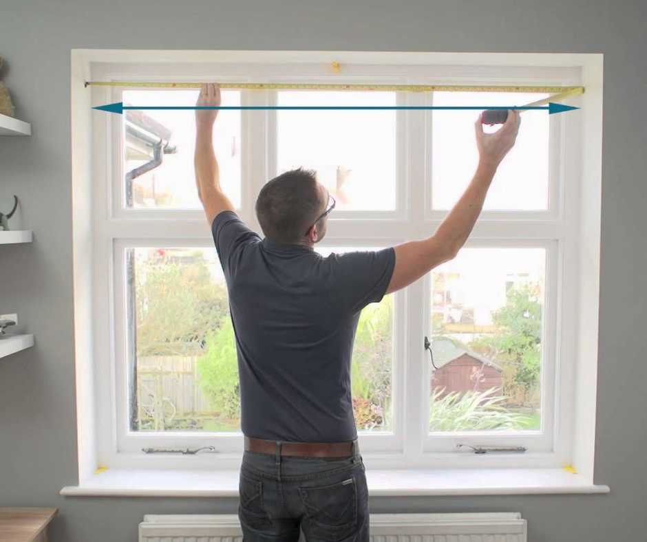 photo of a man measuring a window